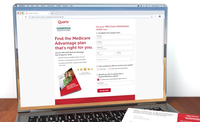 Macbook on a wooden table showing a Quartz landing page for a free plan comparison guide